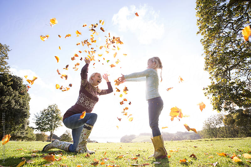 Mother and Daughter playing in garden with autumn leaves.  by Hugh Sitton for Stocksy United