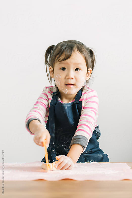 Toddler girl cutting dough by MaaHoo Studio for Stocksy United