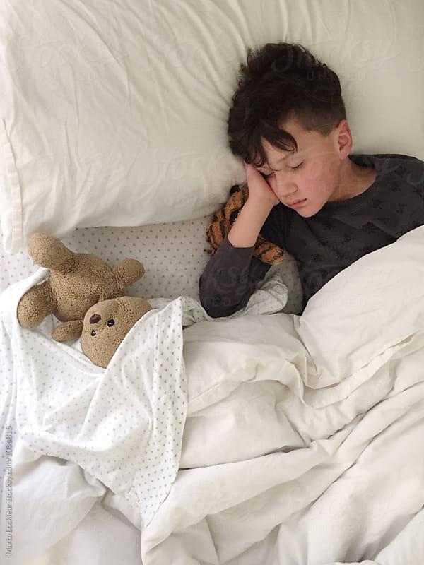 boy asleep with teddy bear by Marta Locklear for Stocksy United