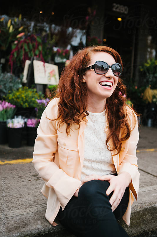 Beautiful woman with red hair sitting outside a flower shop by Kristine Weilert for Stocksy United