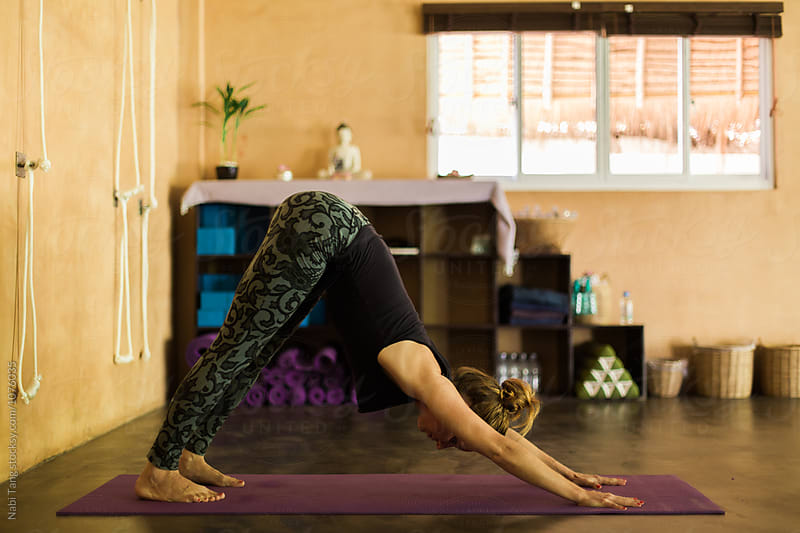 Woman doing downward dog pose in the studio by Nabi Tang for Stocksy United