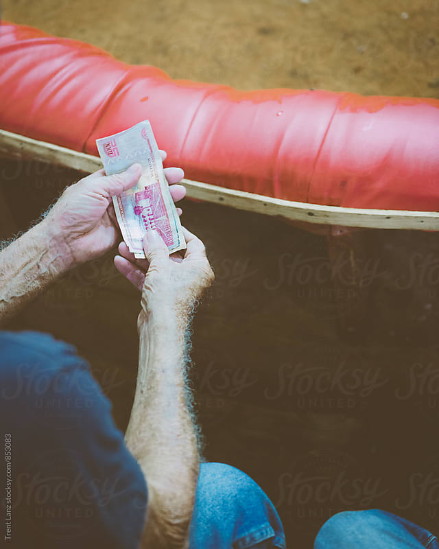 Elderly man holding money by Trent Lanz for Stocksy United