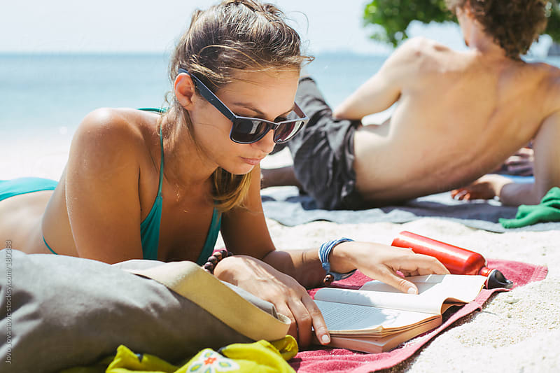 Young woman reading book at tropical beach by Jovo Jovanovic for Stocksy United