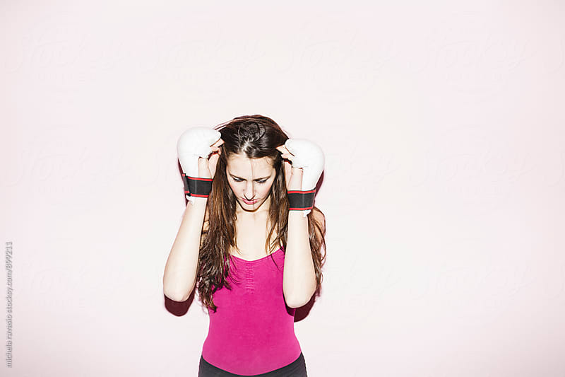 Young woman with kick boxing gloves looking down by michela ravasio for Stocksy United