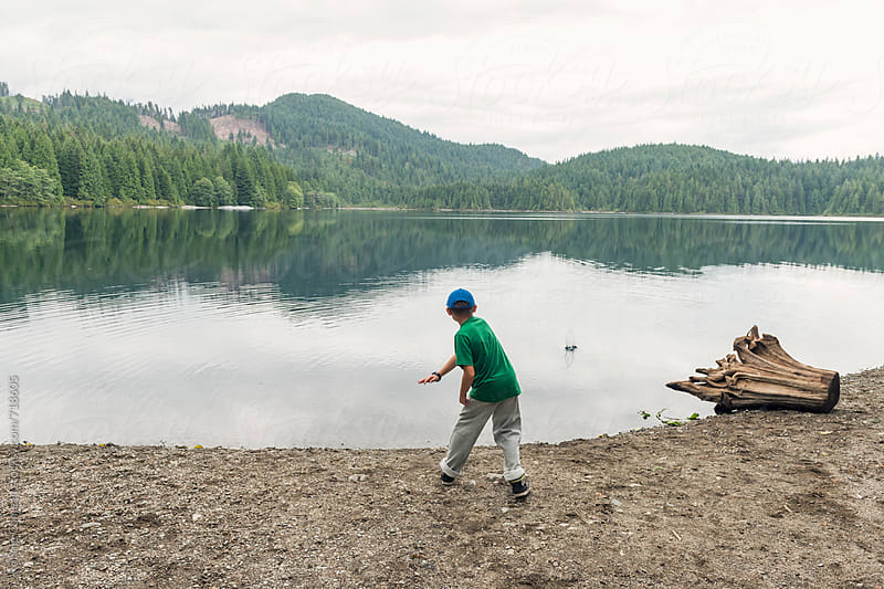Boy Skipping Stones At Lake by Ronnie Comeau for Stocksy United