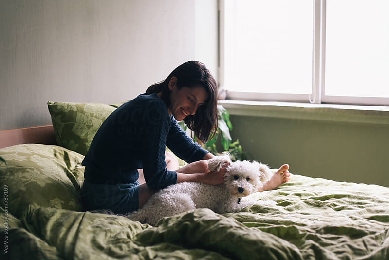 White poodle and young brunette woman on the bed  by Marija Mandic for Stocksy United