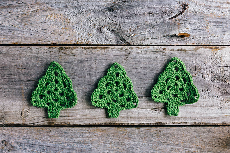 Three little crocheted Christmas trees on rustic wood background by Jacqui Miller for Stocksy United