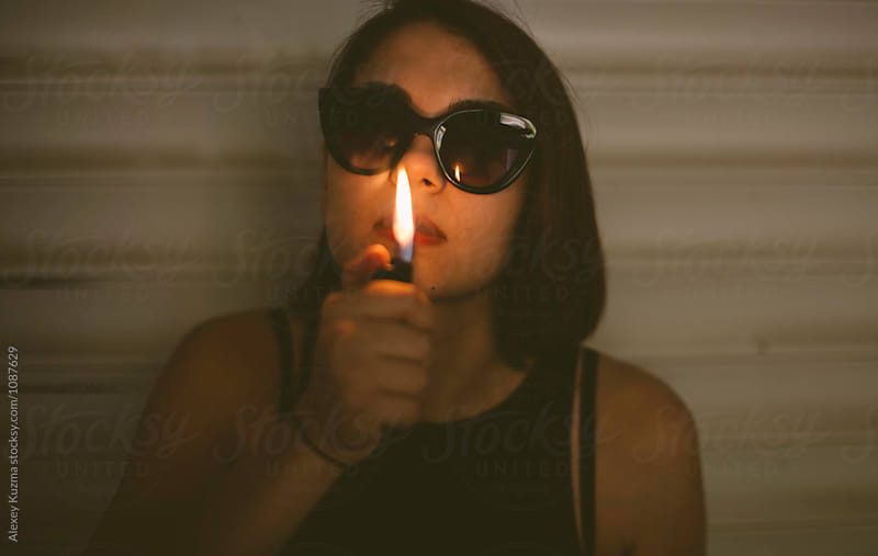 night portrait of young woman with cigarette lighter by Alexey Kuzma for Stocksy United
