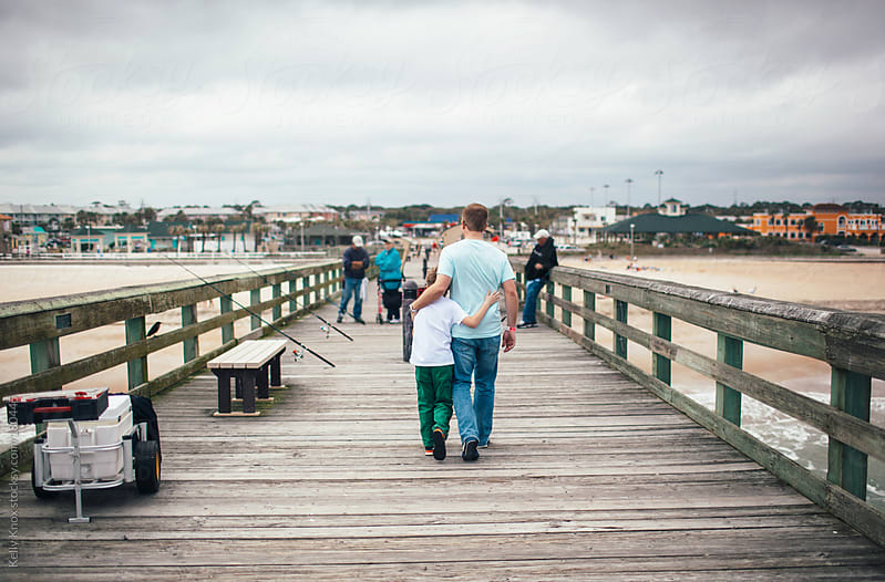 father and son walking on a pier by Kelly Knox for Stocksy United