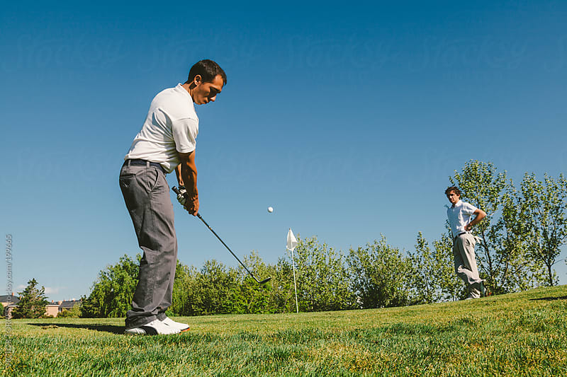 Golfer Trying to Introduce the Ball in the Hole while the other player waits by VICTOR TORRES for Stocksy United