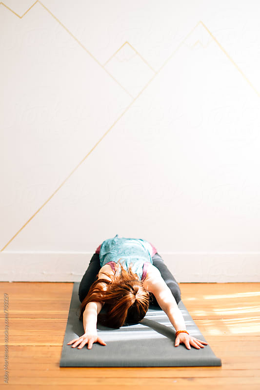 Woman on Yoga Mat in Child's Pose by Abby Mortenson for Stocksy United