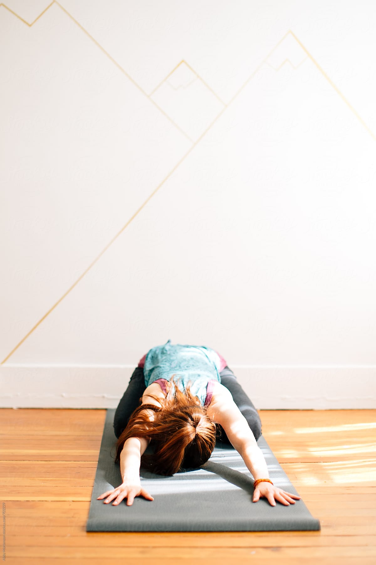 Woman On Yoga Mat In Child S Pose By Abby Mortenson Stocksy United