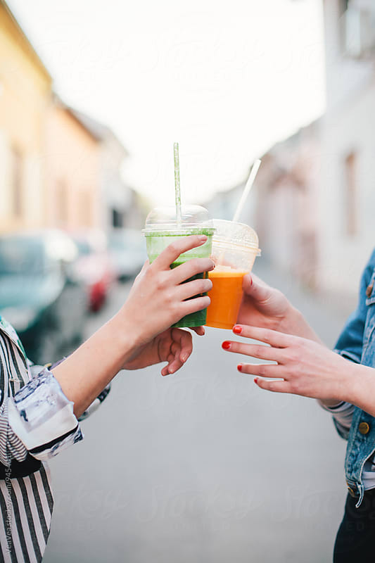 Female hands holding smoothies  by Marija Mandic for Stocksy United