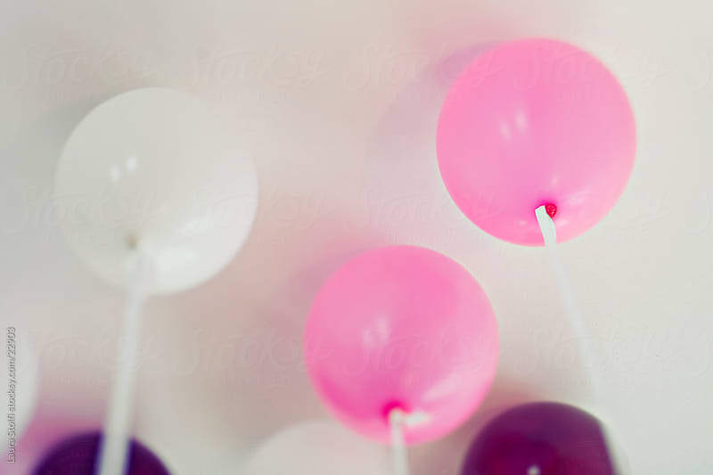 Pink, white and purple balloons touching white ceiling by Laura Stolfi for Stocksy United