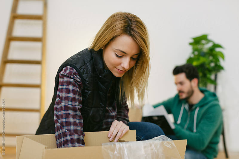 Young couple unpacking cardboard boxes at new home. by BONNINSTUDIO for Stocksy United