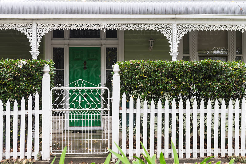 traditional weatherboard house with picketet fence and a hedge by Gillian Vann for Stocksy United