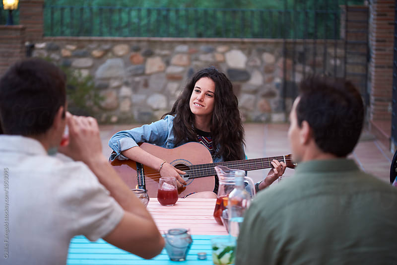 Brunette playing guitar at outdoor party by Guille Faingold for Stocksy United