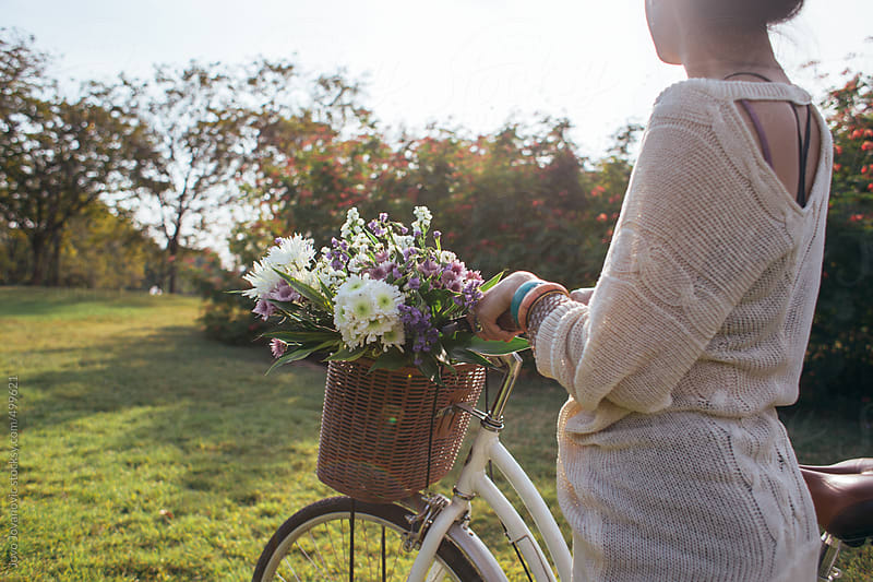 Spring time - woman pushing her bike in a park with a basket full of flowers by Jovo Jovanovic for Stocksy United