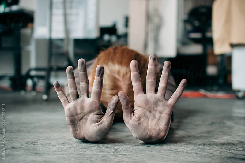Woman lies facedown in art studio, showing off charcoal-covered hands by Kathryn Swayze for Stocksy United