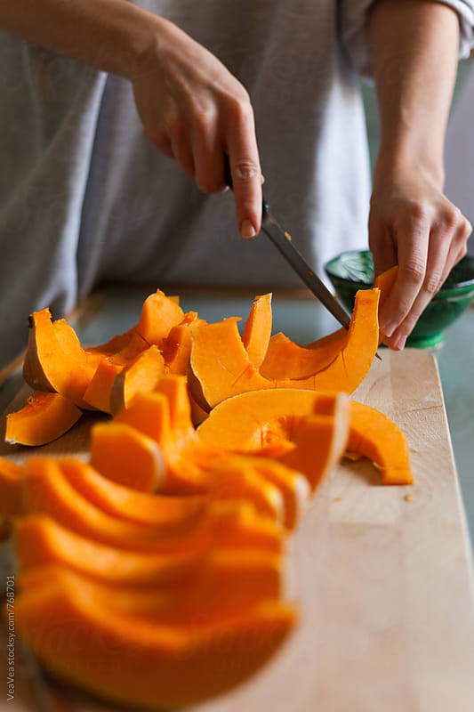 Female hands cutting pumpkin into slices  by Marija Mandic for Stocksy United