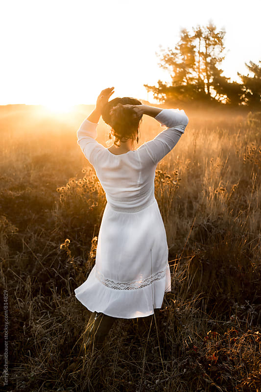 Woman in field at Sunrise by Terry Schmidbauer for Stocksy United