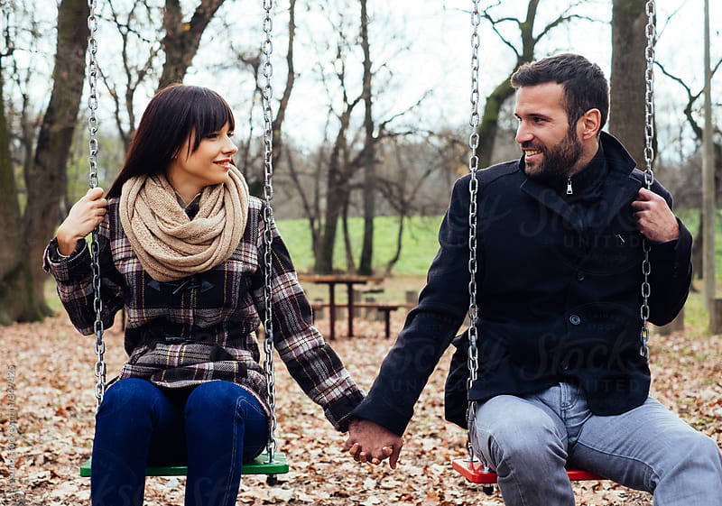 Couple Holding Hands on the Swings by Mosuno for Stocksy United