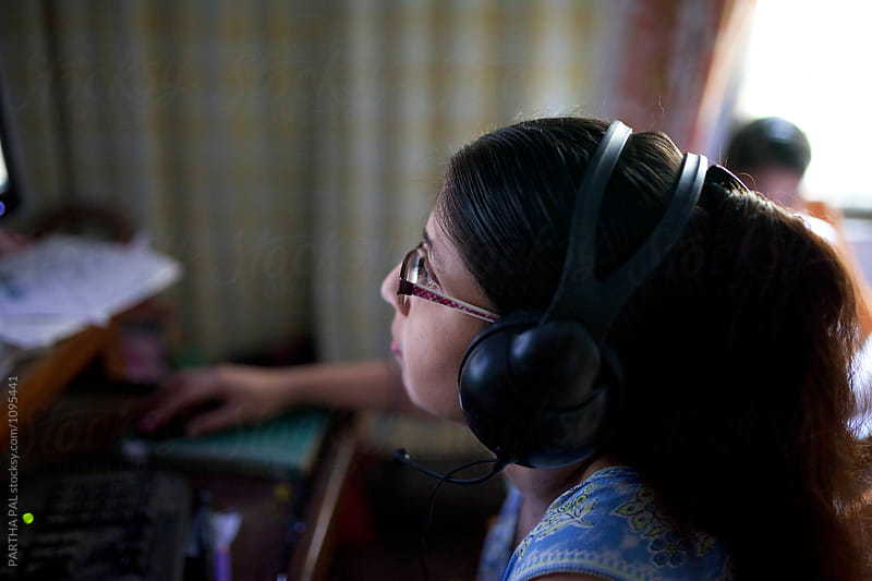 A woman watching movie in desktop with headphone by PARTHA PAL for Stocksy United