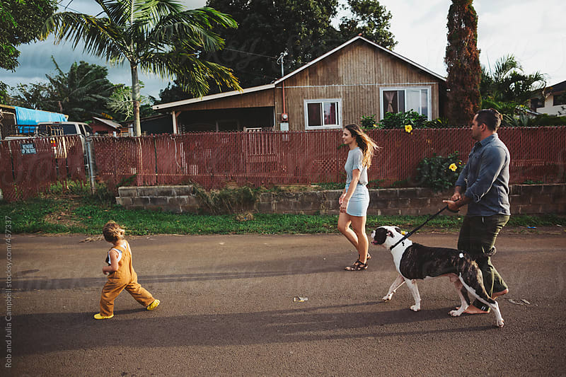 Young, stylish family walking in tropical neighbourhood together by Rob and Julia Campbell for Stocksy United