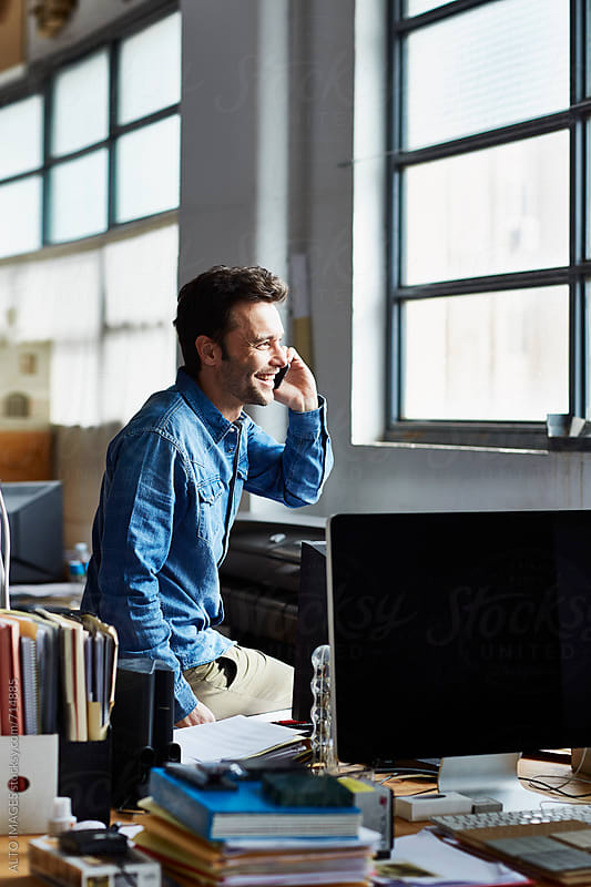 Smiling Businessman Using Smart Phone In Office by ALTO IMAGES for Stocksy United