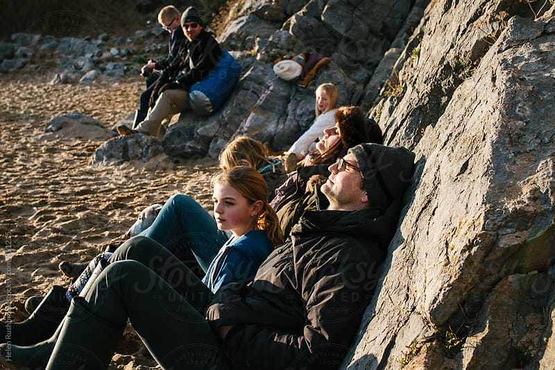 A group of friends sitting in a sunny spot on a beach in winter. by Helen Rushbrook for Stocksy United