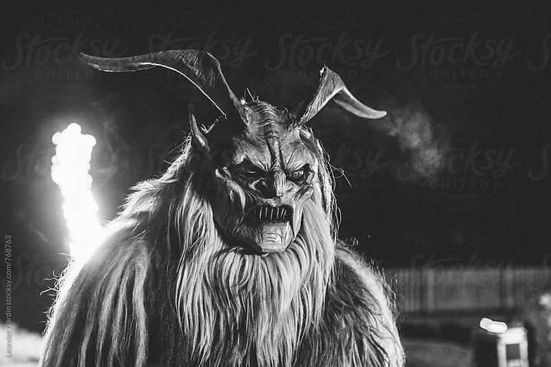 monochrome portrait of a scary looking krampus  by Leander Nardin for Stocksy United