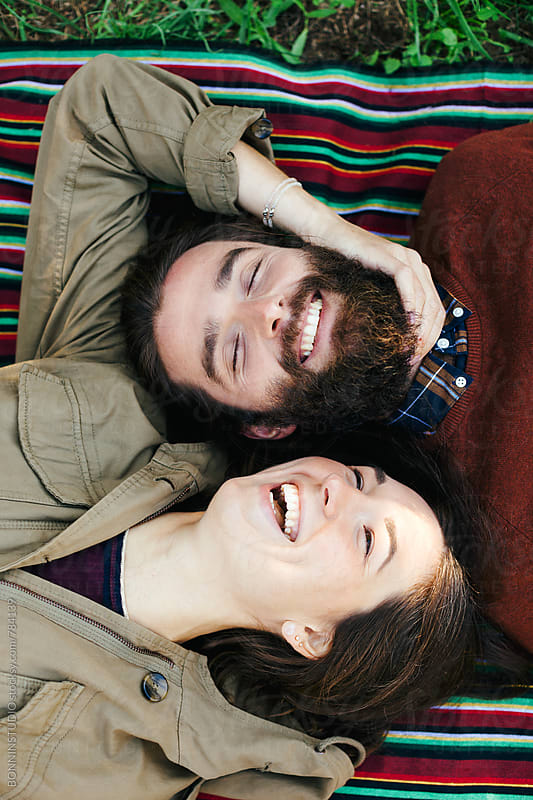 Overhead of a couple laughing resting on a striped blanket in the park. by BONNINSTUDIO for Stocksy United