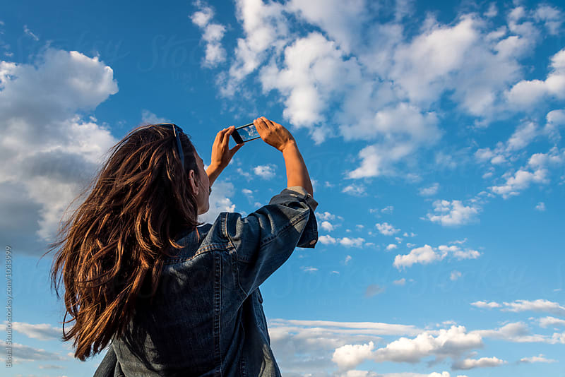 Beauty young woman taking pictures of a cloudy sky with a smartphone by Bisual Studio for Stocksy United