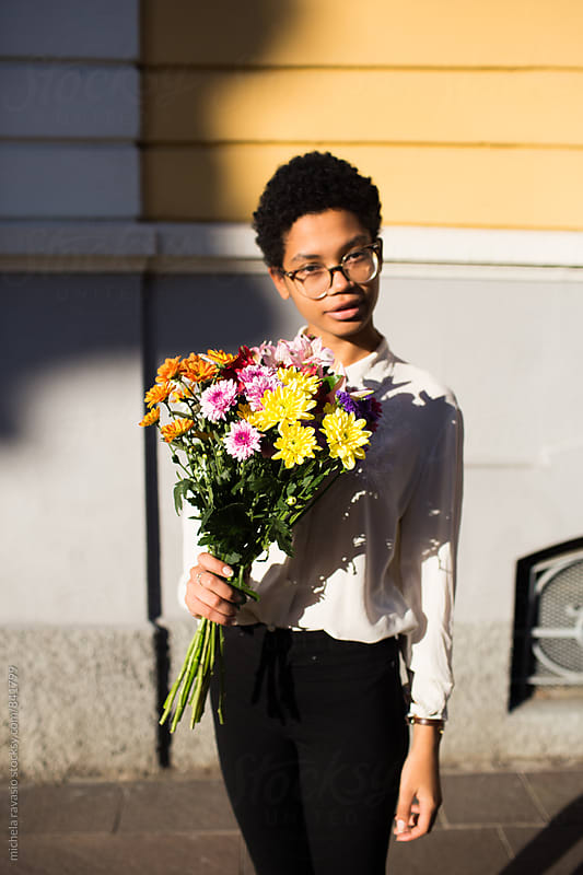 Woman holding a bouquet of colorful flowers by michela ravasio for Stocksy United