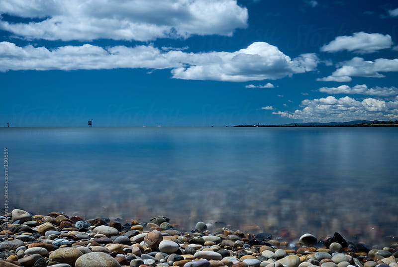 Pebbly beach under a cloudy blue sky by Gary Radler Photography for Stocksy United