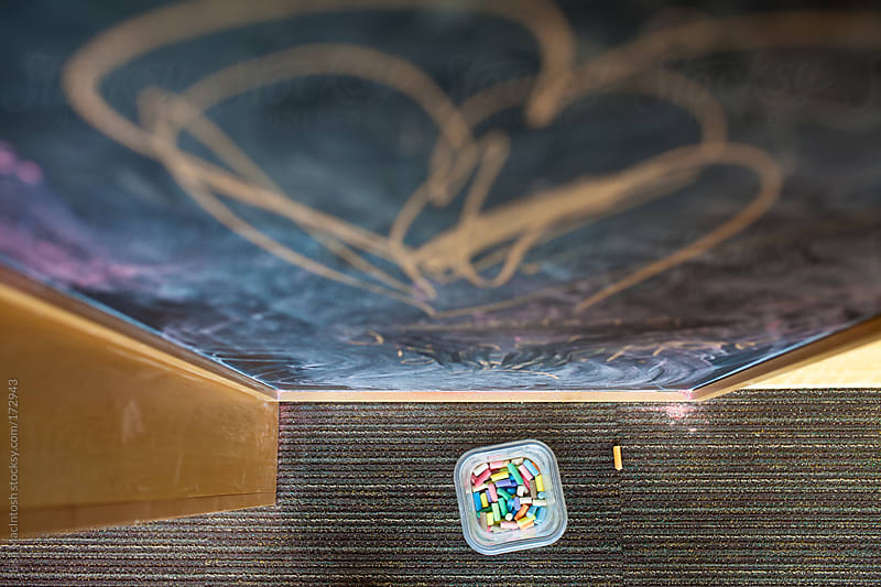 looking down at chalk board and container of chalk on floor by Lisa MacIntosh for Stocksy United