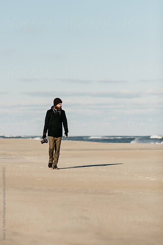 Photographer walking on beach by Isaiah & Taylor Photography for Stocksy United