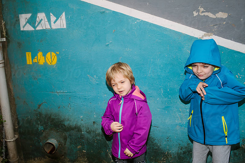 Two brightly dressed funny kids in front of a painted urban wall. by Julia Forsman for Stocksy United