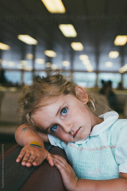 Tired four year old girl resting head on ferry boat seat by Paul Edmondson for Stocksy United