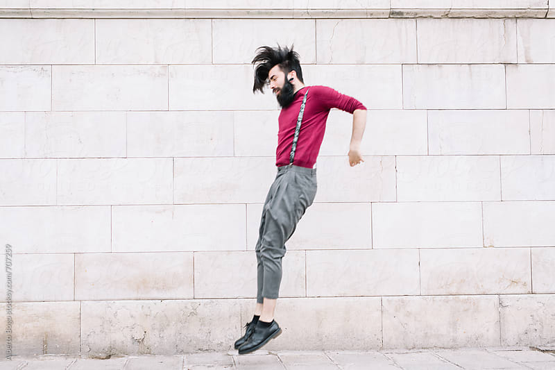 Bearded man jumping against wall by Alberto Bogo for Stocksy United
