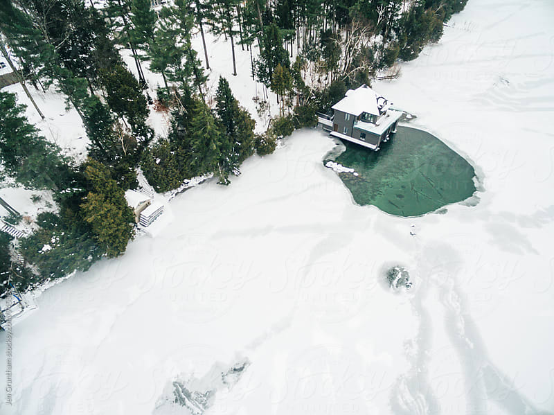 Aerial drone image of a boathouse on a frozen lake by Jen Grantham for Stocksy United