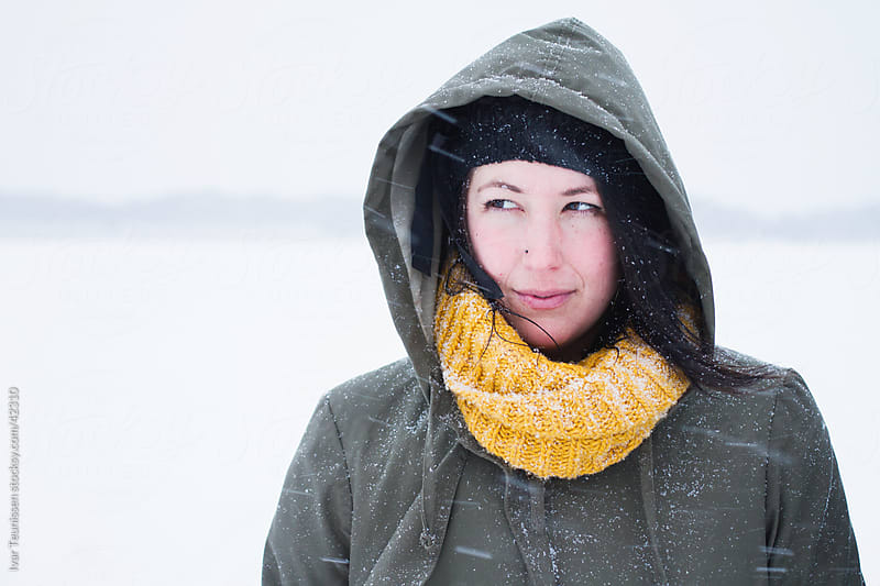 Young woman in snow storm by Ivar Teunissen for Stocksy United