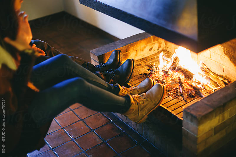 Couple warming up in front of a fireplace at home. by BONNINSTUDIO for Stocksy United