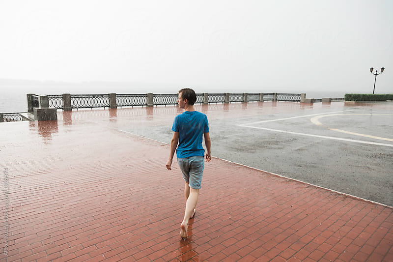 barefooted happy young man walking  under rain by Alexey Kuzma for Stocksy United