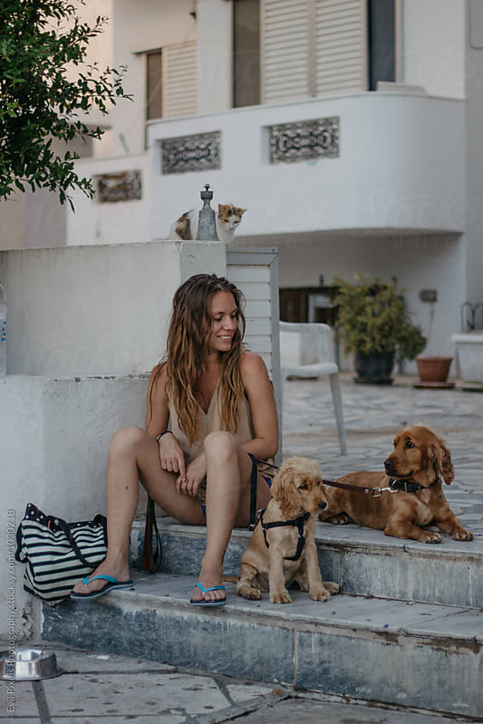 Young female having fun with her cocker spaniels and stray cat  by Branislava Živić for Stocksy United