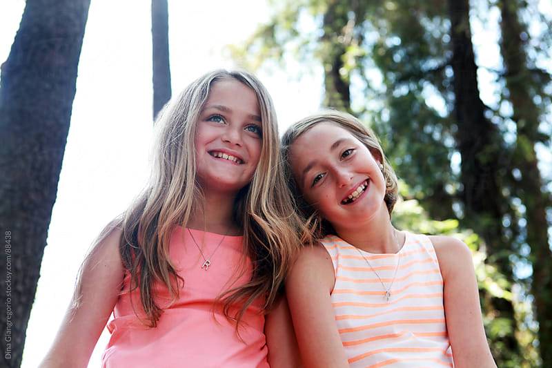 Fraternal twin sisters leaning on one another smiling by Dina Giangregorio for Stocksy United