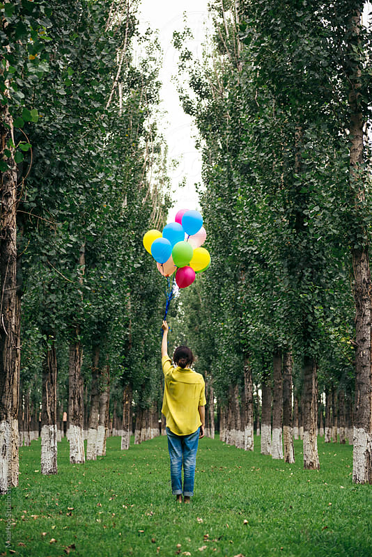 Young woman holding balloons in park by MaaHoo Studio for Stocksy United
