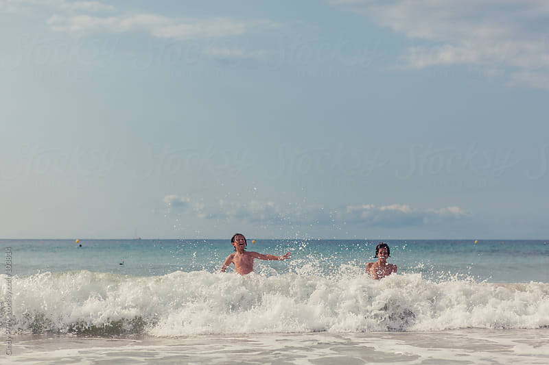 Two boys swimming in the ocean crashing against the waves in the summer by Cindy Prins for Stocksy United