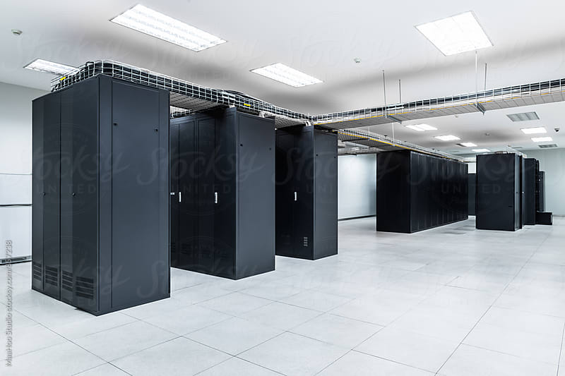 Servers in aisle of storage cabinets in data center by Maa Hoo for Stocksy United