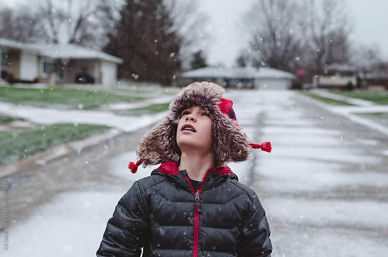 Boy Watches the Snow Fall by Ali Deck for Stocksy United